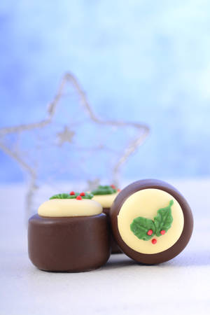 christmastime: Festive Christmas holiday chocolates decorated with green holly leaves and berries. Stock Photo