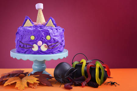 Happy Halloween cat cake party food with purple frosting and candy decorations on colorful party table background. Stock Photo