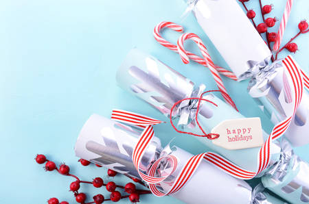 Festive Christmas background with decorated borders of red and white candy canes, bon-bons, berries and Happy Holidays gift tag on a pale blue wood table.