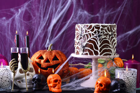 treating: Happy Halloween Party Table with chocolate spider web cake and burning candles against purple spider web background.