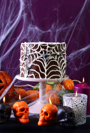 ghoulish: Happy Halloween Party Table with chocolate spider web cake and burning candles against purple spider web background.
