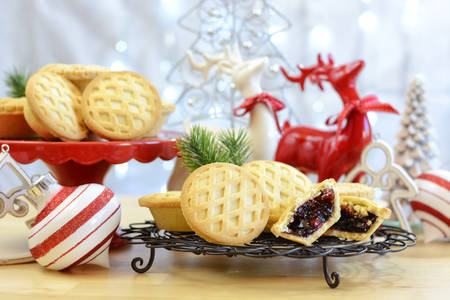 Festive Christmas food table with English style fruit mince pies and reindeer ornaments centrepiece