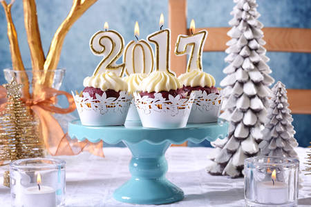 cakestand: Happy New Year 2017 cupcakes on a modern stylish, festive, blue gold and white Winter theme table setting, closeup on cakestand.