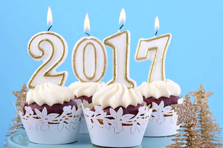 cakestand: Happy New Year cupcakes with 2017 candles in a blue, gold and white winter theme setting background, on cakestand with gold Christmas trees, closeup.
