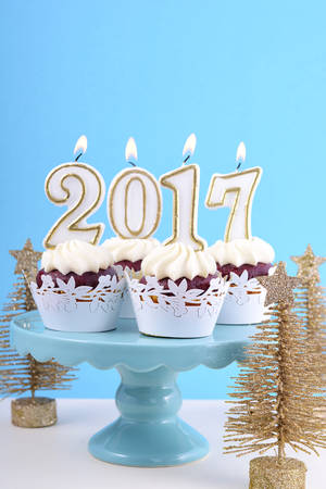 cakestand: Happy New Year cupcakes with 2017 candles in a blue, gold and white winter theme setting background, on cakestand with gold Christmas trees