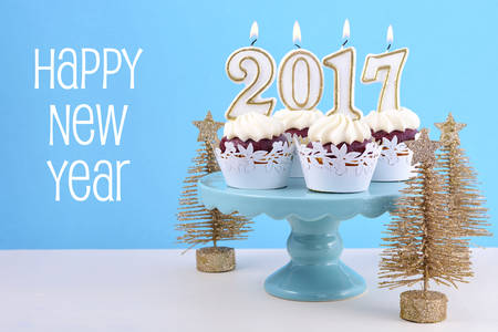 cakestand: Happy New Year cupcakes with 2017 candles in a blue, gold and white winter theme setting background, on cakestand with gold Christmas trees, with copyspace. Stock Photo