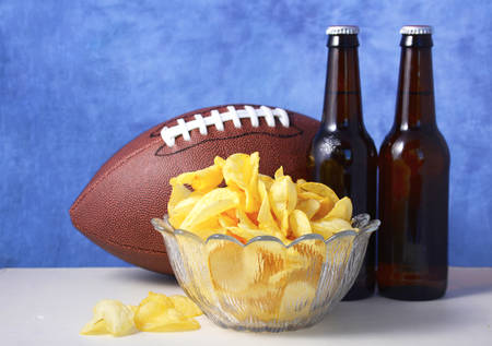 American football with beer and chips on white wood table with blue background. Stock Photo