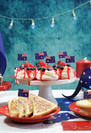 Australian theme party table with flags and iconic food including mini pavlovas, lamingtons, meat pies and fairy bread. Stock Photo