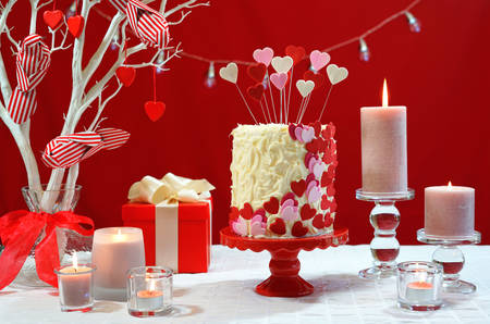 Beautiful St Valentines Day party table with showstopper red, white and pink hearts double layer cake, with white chocolate frosting.