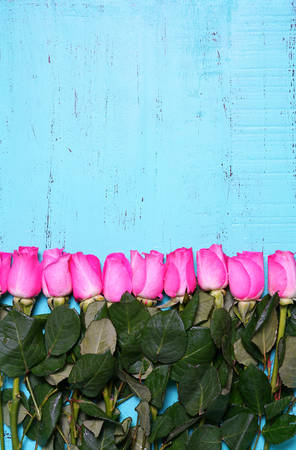 mothering: Vintage aqua blue wood background with decorated borders of pink rose buds with copy space and room for text.