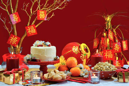 Chinese New Year party table in red and gold theme with food and traditional decorations. Imagens - 70025660