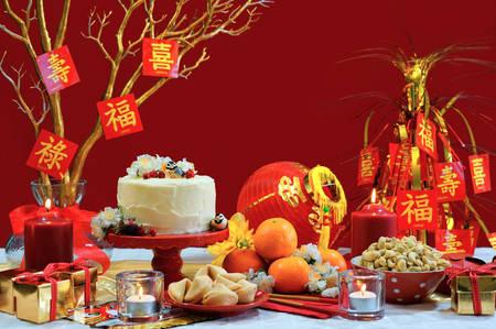Chinese New Year party tafel in de kleuren rood en goud thema met voedsel en traditionele decoraties. Stockfoto