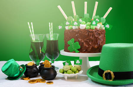 march 17: Happy St Patricks Day, March 17, green and white party table with showstopper chocolate cake decorated with candy, cookies and shamrock flags.