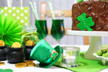 Happy St Patricks Day, March 17, green and white party table with showstopper chocolate cake decorated with candy, cookies and shamrock flags.