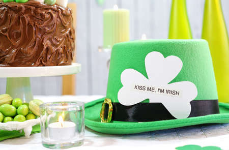 march 17: Happy St Patricks Day, March 17, green and white party table with showstopper chocolate cake decorated with leprechaun hat and Kiss Me I am Irish greeting.