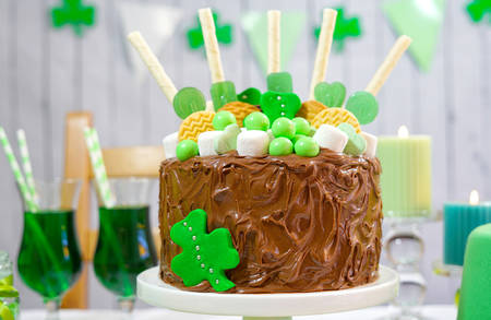17 march: Happy St Patricks Day, March 17, green and white party table with showstopper chocolate cake decorated with candy, cookies and shamrock flags.