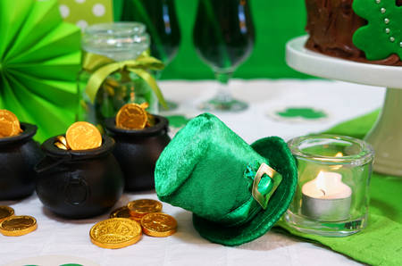 Happy St Patricks Day, March 17, green and white party table, closeup on Leprechaun hats.