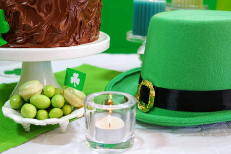 kiss biscuits: Happy St Patricks Day, March 17, green and white party table, closeup on Leprechaun hats.