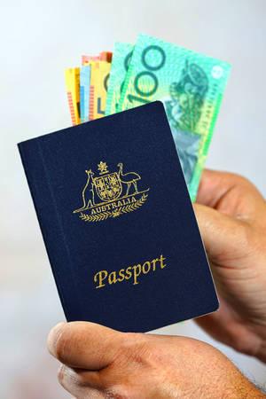 room for your text: Man putting Australian cash money into an Australian passport, vertical. Stock Photo