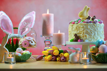 Happy Easter party table with white chocolate bunny novelty cake against a pink background.