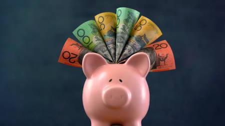 Roze Piggy bank geld concept op donkerblauwe achtergrond, gevuld met Australische contanten. Stockfoto