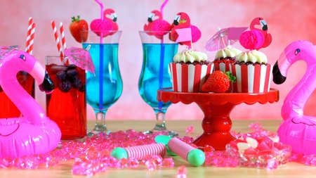 Summer party table with pink flamingo theme, ice cream cones, cupcakes and cocktails,