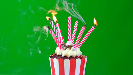Happy Birthday cupcake with colorful candles against a green background, blowing out candles
