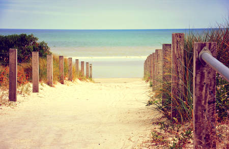 exhilarating: Retro vintage filter sandy path with wooden rails leading down to beautiful blue ocean beach.
