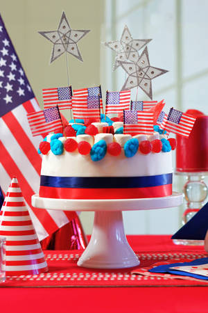 USA National holiday celebration party table with showstopper cake and flags, vertical. Stock Photo