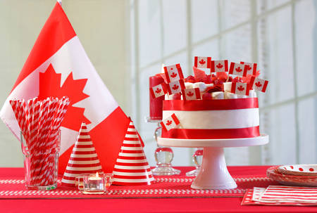 Canada Day national holiday celebration party table with showstopper cake and flags.