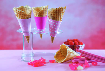 Summertime pink ice cream cones decorated with candy and fruit, meling against a bright pink background.