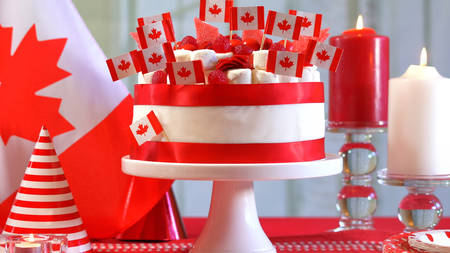 Canada Day national holiday celebration party table with  cake and flags. Stock Photo