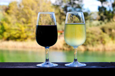 Two glasses of red and white wine on wooden rail overlooking Australian country setting.