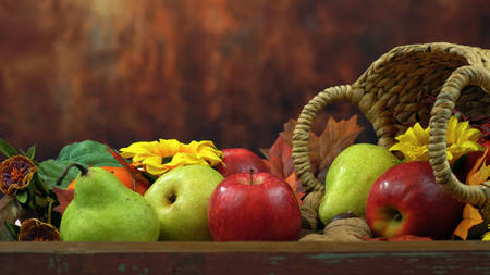 Autumn Fall close up of seasonal fruit and nuts in a basket against a rustic wood background.