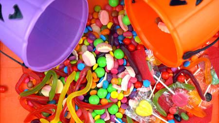 Happy Halloween Trick or Treat candy overhead jack-o-lantern buckets on bright orange wood table background. Stock Photo