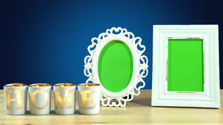 Row of shabby chic photo frames with blank green screens and burning home etched candles in elegant table interiors display Stock Photo