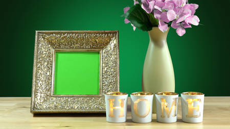 Antique photo frame with blank green screen and vase of flowers withburning home candles in elegant table interiors display