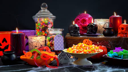 Halloween trick or treat party table with bowls and apothecary jars of candy with skull candles against a black background Stock Photo