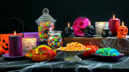 Halloween trick or treat party table with bowls and apothecary jars of candy with skull candles against a black background, with copy space.