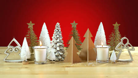 Christmas centerpiece or mantel decoration of rows of minature Christmas Trees with burning candles against a red background.