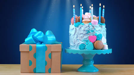 candle: Blue birthday celebration showstopper cake decorated with candy, marshmallows and macarons cookies, and gift highlighted by glittering light stream. Stock Photo