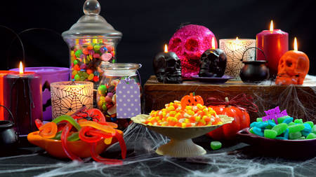 candle: Halloween trick or treat party table with bowls and apothecary jars of candy with skull candles against a black background Stock Photo