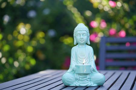 candle: Aqua blue Buddha statue in colorful garden setting Stock Photo