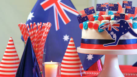 Australian celebration party table with showstopper cake decorated with candy, stars and flags, close up.