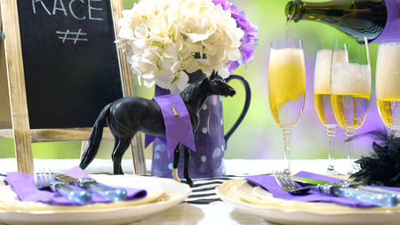 Horse racing Racing Day Luncheon fine dining table setting with small black fascinator hat, decorations and champagne, pouring champagne. Stock Photo