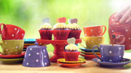Colorful Mad Hatter style tea party with cupcakes and rainbow colored polka dot cups and saucers, with bokeh garden background and lens flare, pouring tea. Stock Photo