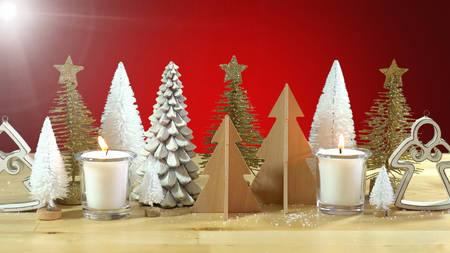 Christmas centerpiece or mantel decoration of rows of minature Christmas Trees with burning candles against a red background, with light flare.