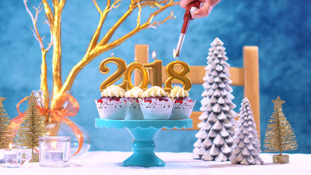 Happy New Year 2018 cupcakes on a modern stylish, festive, blue gold and white Winter theme table setting, lighting candles.