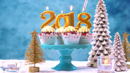 Happy New Year 2018 cupcakes on a modern stylish, festive, blue gold and white Winter theme table setting, close up with copy space lighting candles. Stock Photo