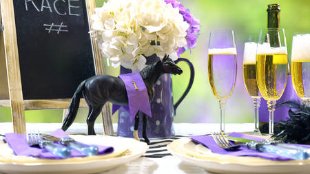 Horse racing Racing Day Luncheon fine dining table setting with small black fascinator hat, decorations and champagne. Фото со стока